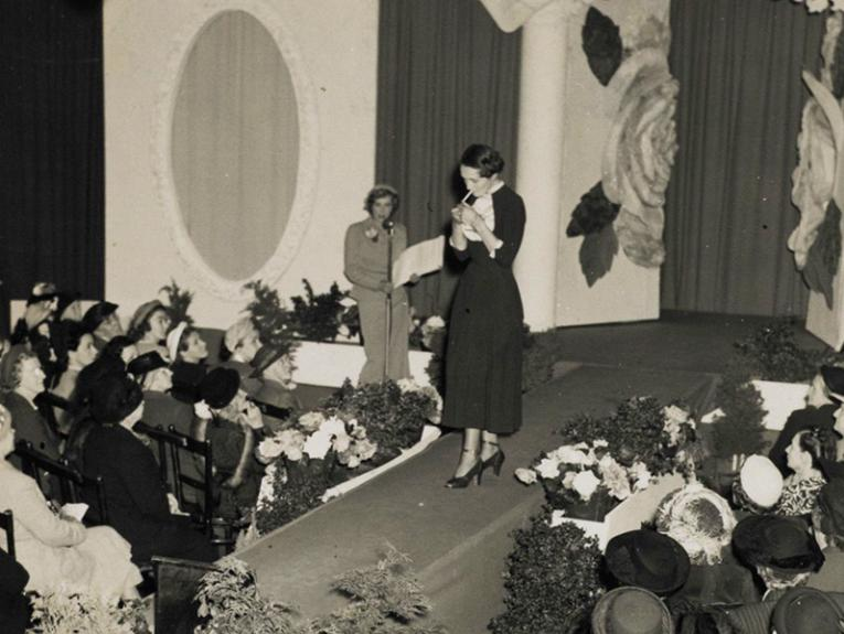 A black and white photo of a woman lighting up a cigarette on the catwalk