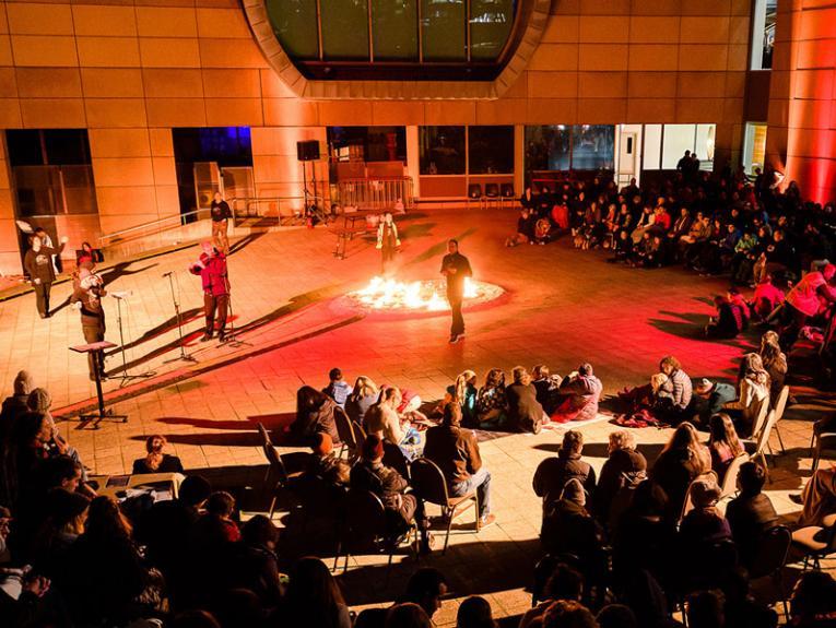 A crowd sat round a fire