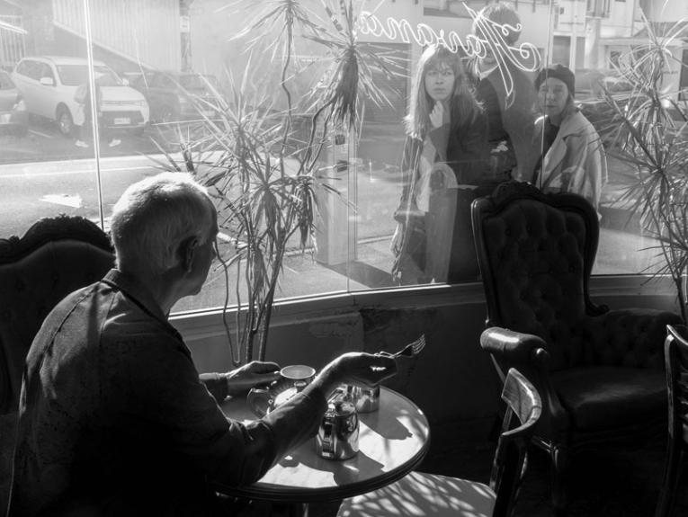 Black and white photo of a man in a cafe, passes by look through the windows