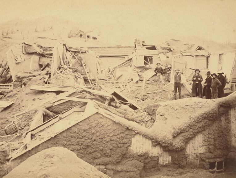 Sepia photo of two people standing on the ruins of a shed covered in mud