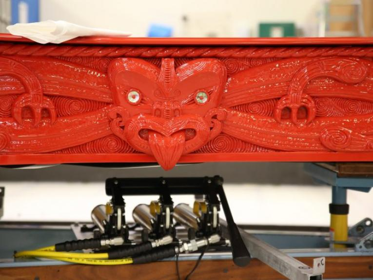 Close-up of carving on a red piano with Māori design