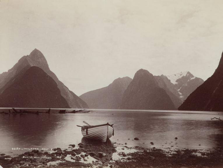 Black and white photograph of Milford Sound with a rowing boat in the foreground