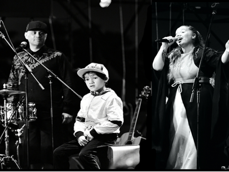 A black and white video of two adults and a child playing music on a stage