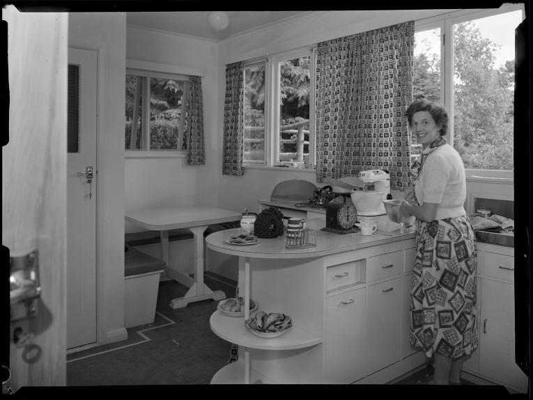 A black and white photo of a woman in a kitchen in the 50s