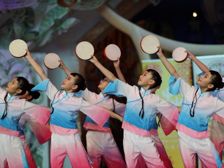 Children in blue and pink matching suits holding tambourines in the air