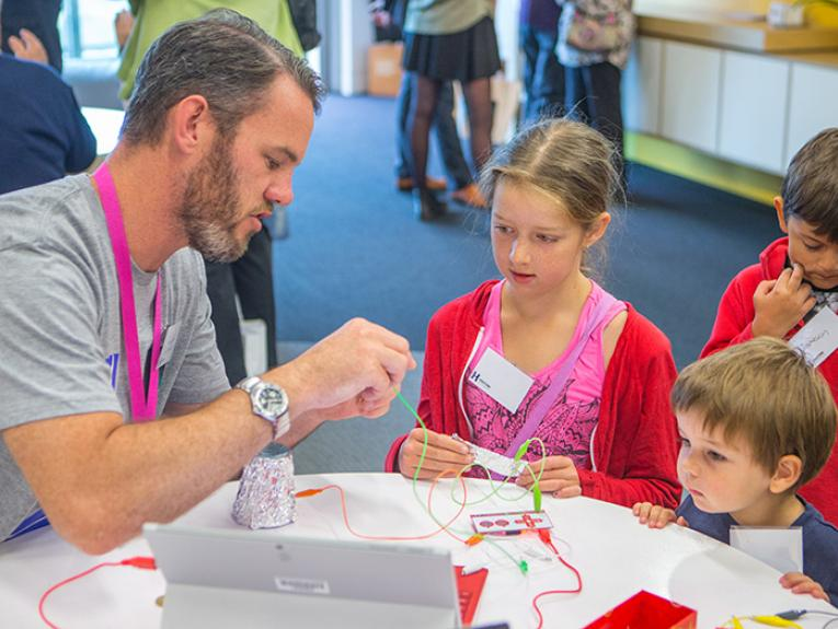 An educator leads children in making electronic musical instruments