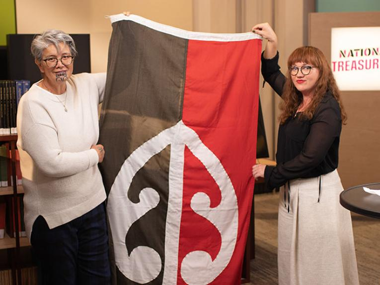 Two women holding up a flag