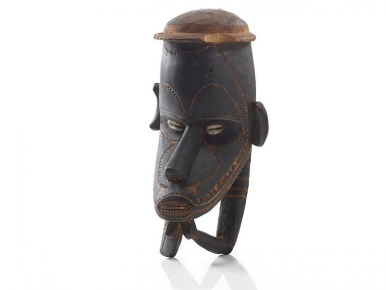A carved wooden head. The eyes are made of shells, and the head is wearing a hat