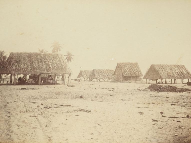 Sepia photograph of huts with people sat under them