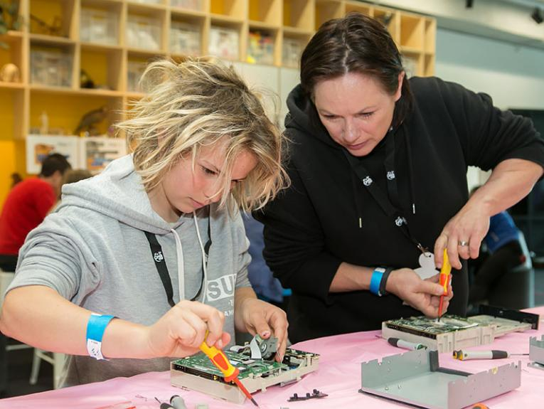 Young girl and woman take apart optical drives