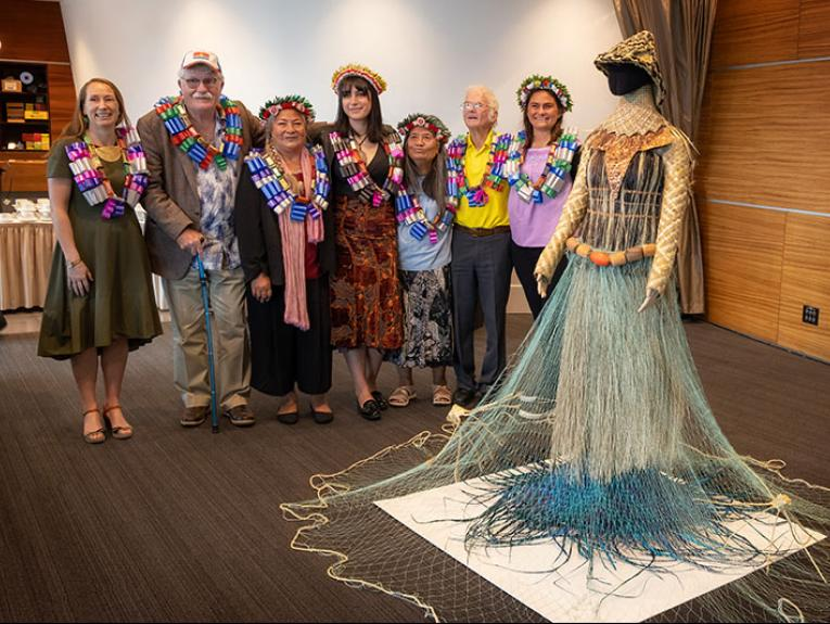 Seven people stand with the woven garment adorned over a mannequin