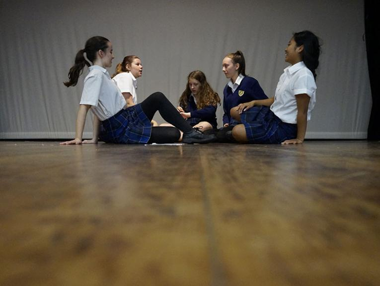 Students sit on a stage