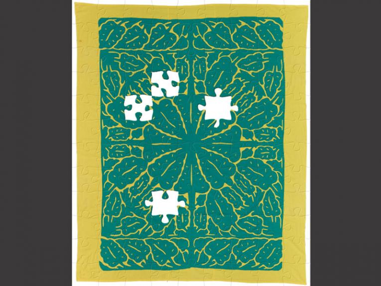 Puzzle of a turquoise and yellow patterned quilt with leaves on it