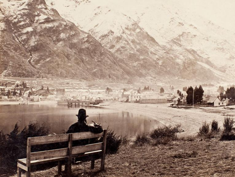 A black and white photo of a man sitting on a bench overlooking Lake Wakatipu, he wears a hat and is reading a book