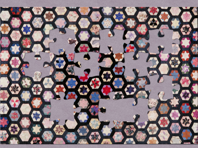 A colourful quilt with hexagonal shapes and jigsaw pieces cut out of it