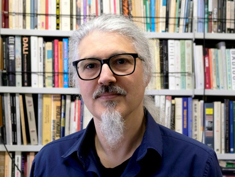 A man with white hair and a beard in front of a bookcase
