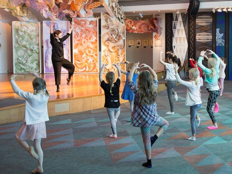 Group of children practice a ballet pose, prompted by a member of Royal New Zealand Ballet