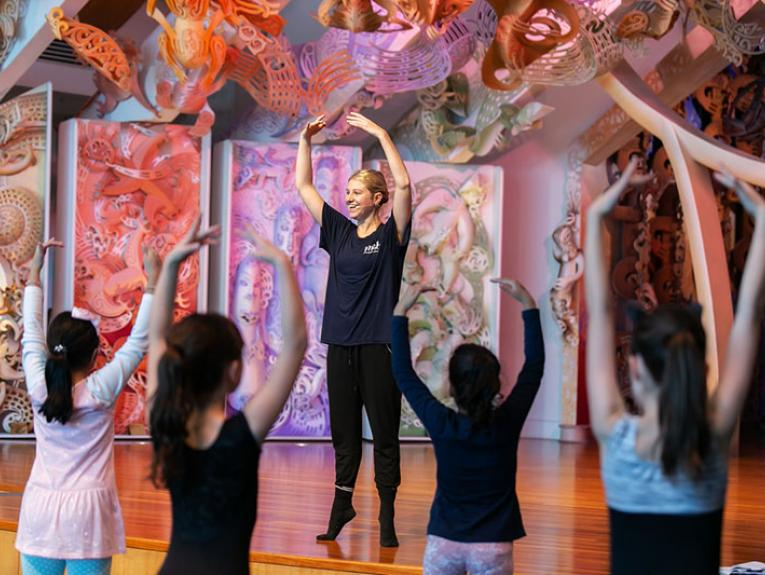 A member of the Royal New Zealand Ballet teaches a group of children how to dance