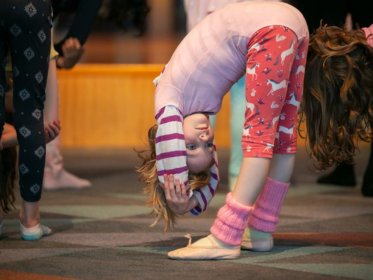A child in a ballet leotard and ballet shoes is bent over double in a dance position