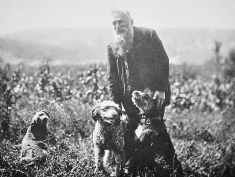Auguste Rodin surrounded by three dogs