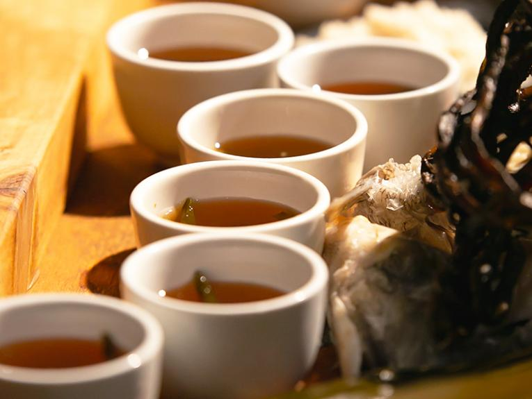 small cups of tea sitting on a wooden tray next to some seaweed