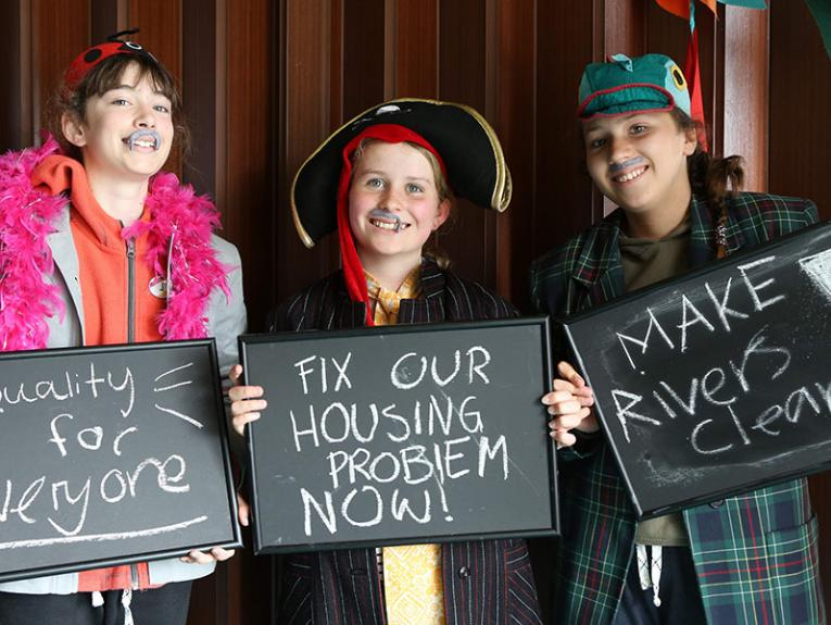 Three girls hold up signs that read 'Equality for everyone', 'Fix our housing problem now', and 'Make rivers clean'