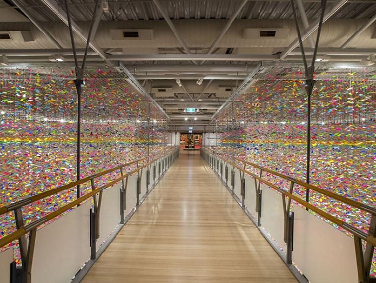 Hundreds of thousands of brightly coloured plastic tabs hang in strands on either side of a walkway bridge in an art gallery.