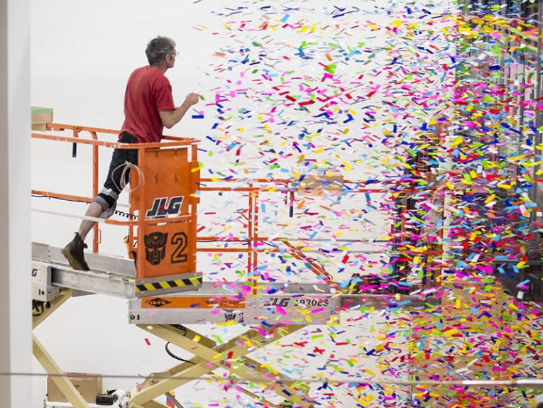 A man stands on a scissor lift hanging strands of coloured plastic from the ceiling while a woman below holds the strand so it doesn't get tangled