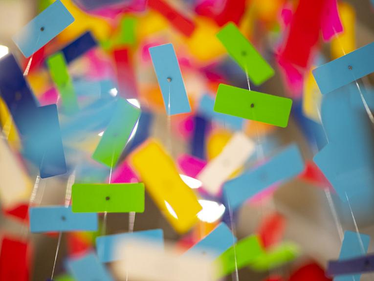 An extreme close-up of brightly-coloured pieces of plastic suspended from the ceiling