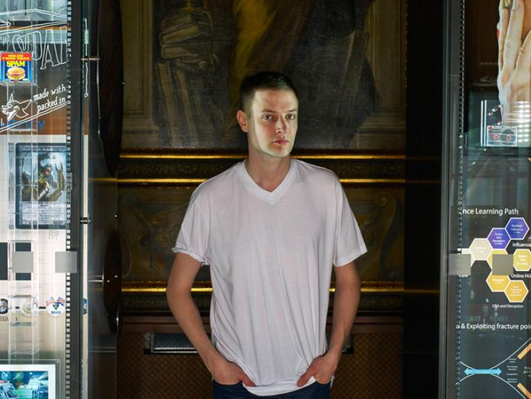 Portrait of Simon Denny standing near his exhibition titled Secret Power