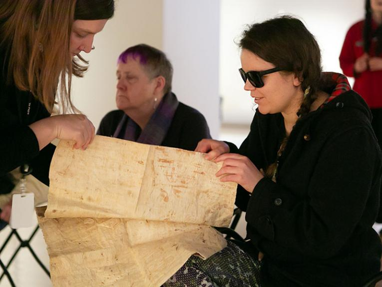 Two women, one in dark glasses, hold a large sheet of tapa between them, pinching the edge to feel its thickness