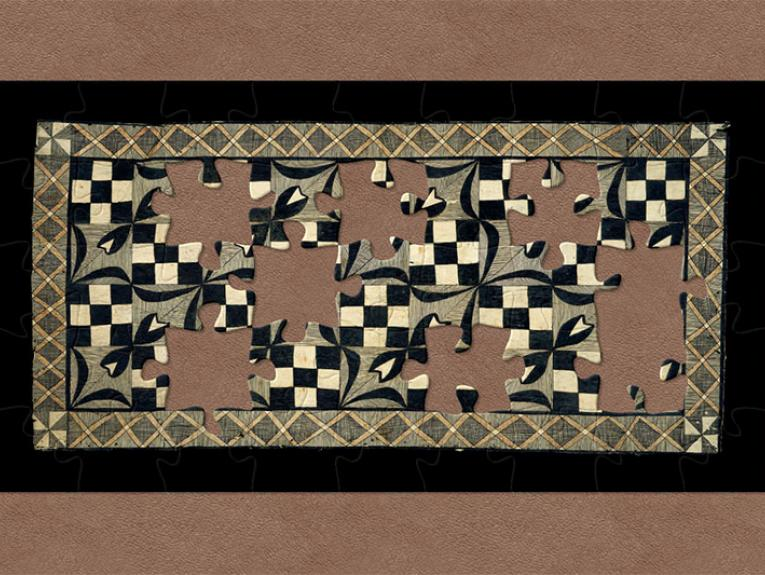 Tapa cloth. The border is a network of orange Xs, while the internal patterns alternate between checkerboards and flowers