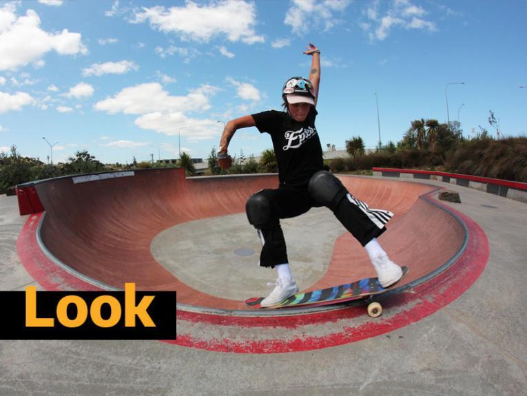 A woman making a jump on a skateboard in a skate park