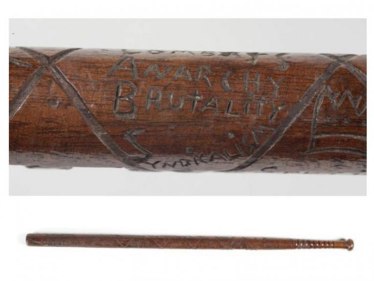 A closeup photo of inscription on a wooden baton, saying 'Combats anarchy, brutality, socialism'. The full baton is shown below.