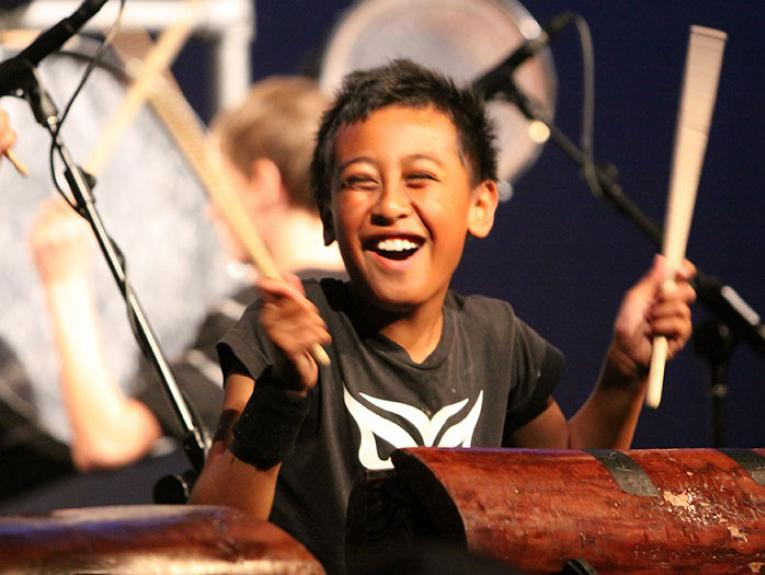 Photo of child playing a percussion instrument