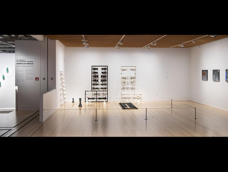 General view of the Surrealist Impulse exhibition. One work, of four men, hangs in a stairwell, one sculpture of a chess set stands on the floor leaning against the wall, and three square paintings also hang on a wall
