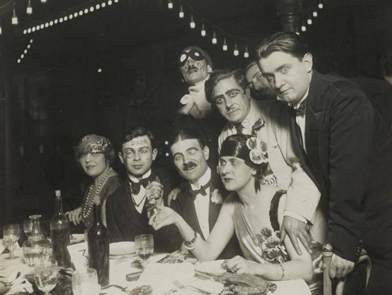 A black and white photo of eight people in makeup and 20s clothing looking at the camera in a variety of ways