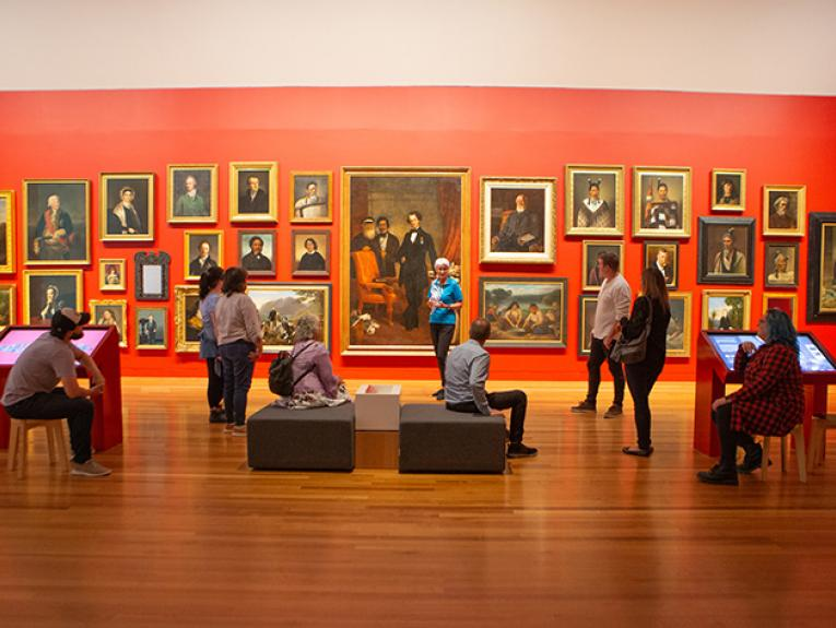 A group of people standing and sitting in front of art portraits on a red wall