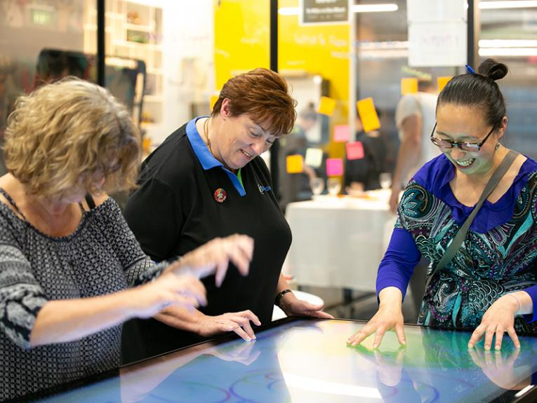Three people sitting around a large touchscreen and looking at it