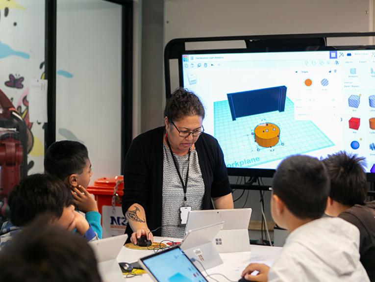Haley uses a computer, which displays on a large screen behind her, to teach a group of children who are sitting around a table