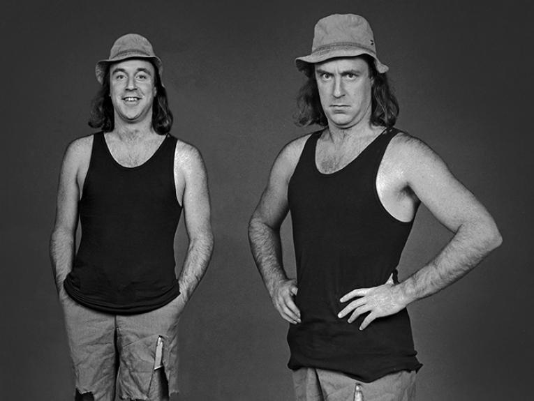 Comedian John Clarke in character as Fred Dagg wearing gumboots, tight shorts, and a floppy hat