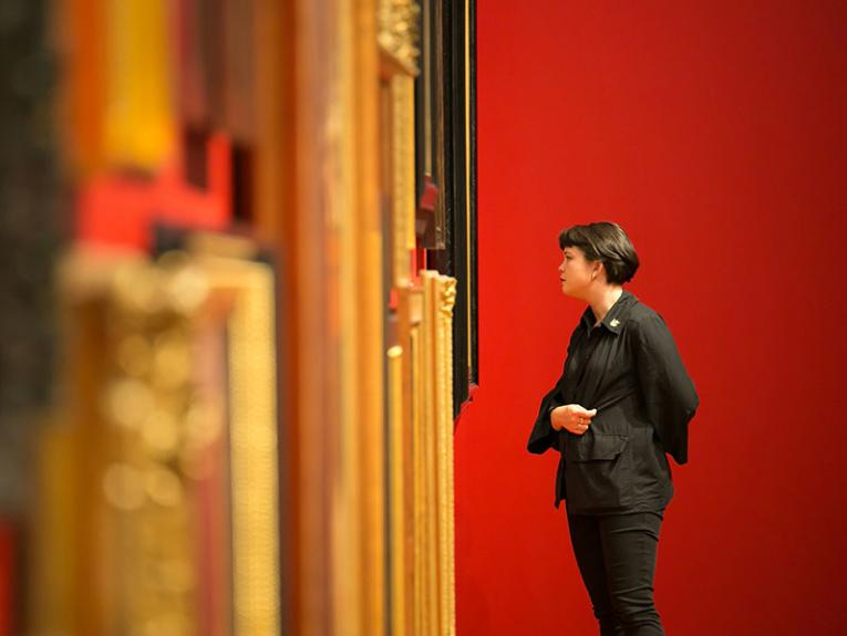 A woman looks at a wall of portraits