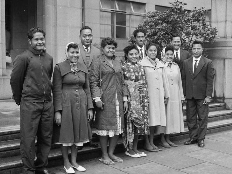 A black and white photo of a group of adults standing on some steps smiling