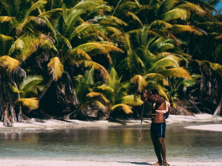 A man on a tropical island holds a rod
