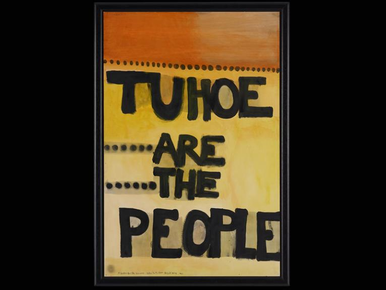 A yellow and orange canvas with the words 'Tuhoe are the People' on it