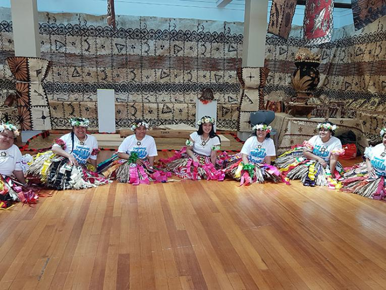 A group of women in Tuvalu skirts sit on the floor. Behind them apa adorns the walls