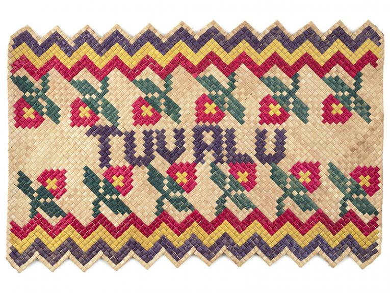 A woven mat with red, green, yellow and purple colours and the word Tuvalu woven into it