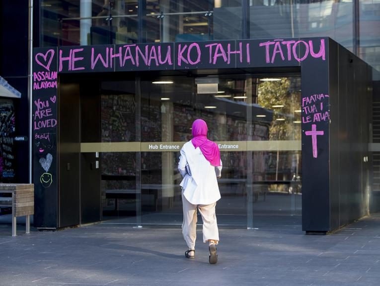A woman in a pink hijab walking into a glass-walled building with pink writing surrounding the doorway
