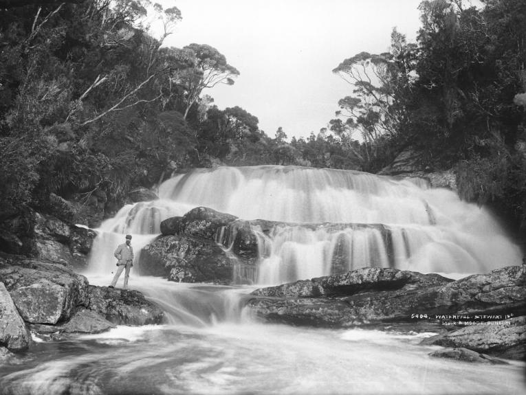 Black and white photo of a man standing in front of a large waterfall