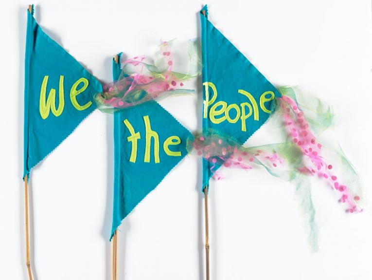 Blue flags which say 'We the People'.